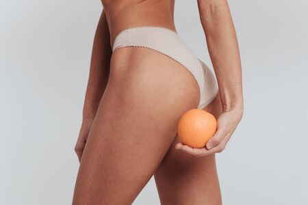 Side turn. Particle photo of girl in white underwear standing at white background and holding orange.