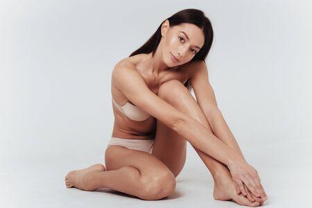 Beautiful brunette in white underwear model sitting at the white background. Zdjęcie Seryjne - 134741973