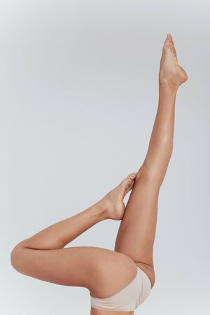One of the fitness exercises. White underwear. Photo of female slim legs raised up indoors on the white background.