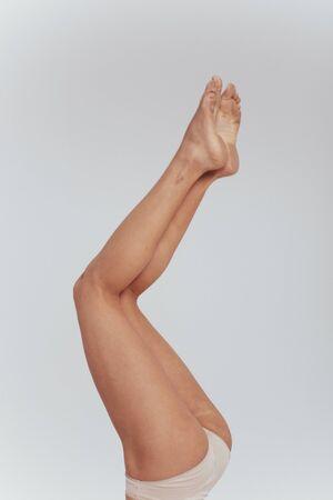 Photo of female slim legs raised up indoors on the white background.