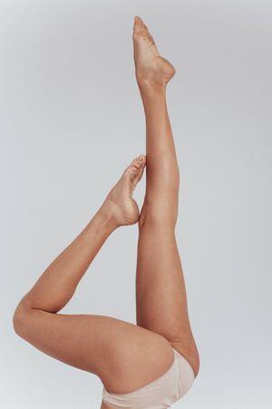 Almost naked. Photo of female slim legs raised up indoors on the white background. Zdjęcie Seryjne - 134741979
