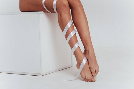 Female legs in the white interior with ribbons over. Cropped photo.