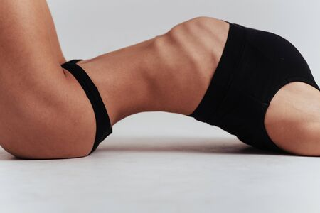 Side photo of the womans body in the black underwear lying down. Stock Photo