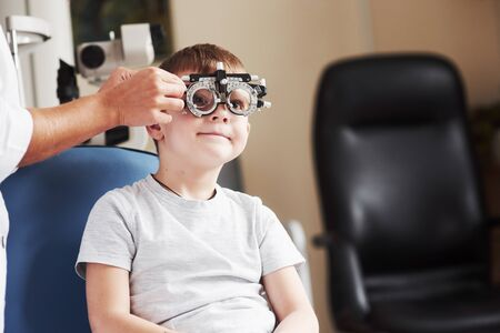 Checking different lenses. Child sitting in the doctors cabinet and have tested his visual acuity.