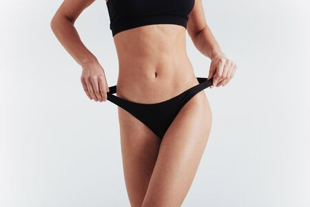 Front view. Girl in underwear with slim figure shows her body at the white background.