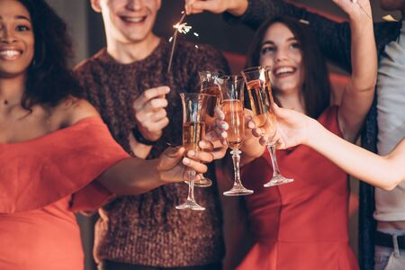 Champagne is an integral part. Multiracial friends celebrate new year and holding bengal lights and glasses with drink. Imagens