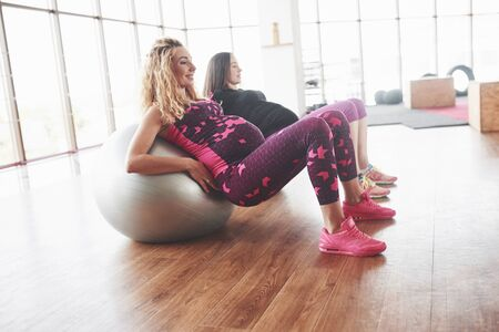 Side photo of two pregnant women doing fitness exersices using stability balls. Stock Photo