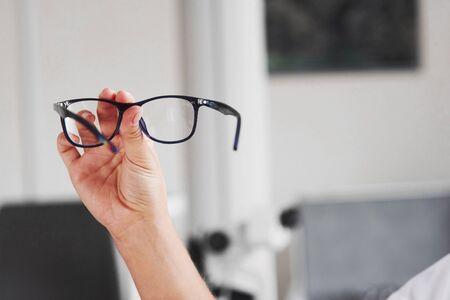 Fokussiertes Foto. Frauenhand hält die blaue Brille im Arztkabinett.