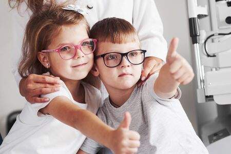 Female doctor hugs her little patients. Glasses are perfectly selected. Stok Fotoğraf