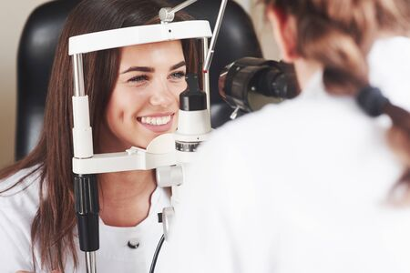 Eyes are in perfect condition. Optometrist checking vision of young beautiful woman.