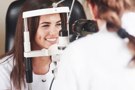 Los ojos están en perfecto estado. Optometrista comprobando la visión de la joven y bella mujer.
