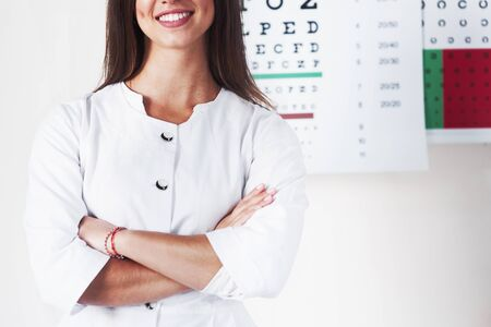Cropped photo of gorgeous female ophthalmologist standing in the background of board with letters. Stockfoto