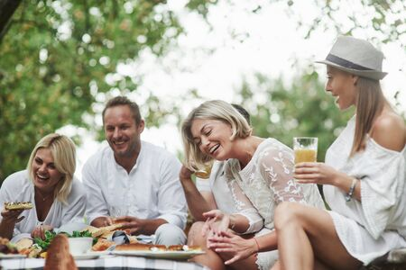 Good friends sit outdoors near the table with food, have dinner and laughing.