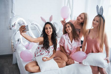 Balloons and bunny ears. Bachelorette party. Four girl in pink and white clothes sits at the sofa and take selfie. Zdjęcie Seryjne