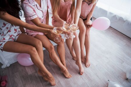 Holding glasses. Legs and bodies only. Celebrating bachelorette in white bedroom. Girls with champagne.