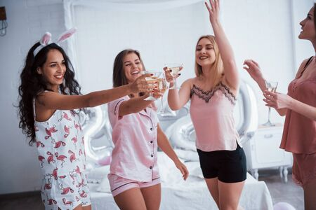 Friends celebrating bachelorette in pajamas in the white room at daylight.