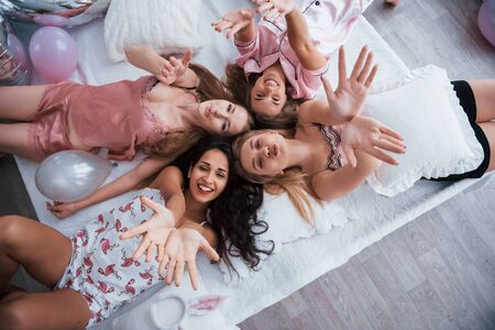 Top view of young girls at bachelorette party lying on the sofa and raising their hands up.