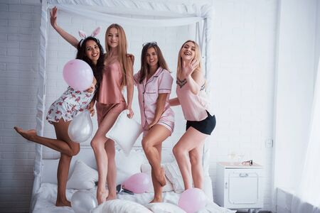 Posing for the picture. Standing on the luxury white bad at holiday time with balloons and bunny ears. Four beautiful girls in night wear have party. Zdjęcie Seryjne