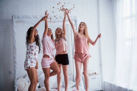 Confetti in the air. Young girls have fun on the white bed in nice room. Zdjęcie Seryjne