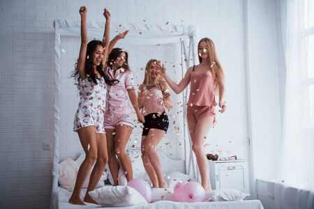 The party is in full swing. Confetti in the air. Young girls have fun on the white bed in nice room.