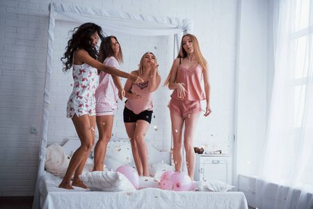 Pink balloons and other holiday stuff. Confetti in the air. Young girls have fun on the white bed in nice room.
