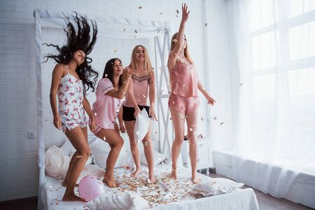 These people know how to party. Confetti in the air. Young girls have fun on the white bed in nice room. Zdjęcie Seryjne
