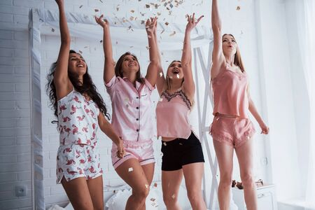 Raise up hands as high as possible Confetti in the air. Young girls have fun on the white bed in nice room.