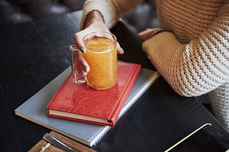 Close up photo of the orange drink that holds by woman hand and stands on the book with red cover. 스톡 콘텐츠 - 134746838