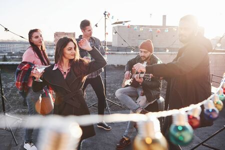 Enjoying the latest warm sunlight. Light bulbs all around the place on the rooftop where is young group of friends have decided spend their weekend with guitar and alcohol.