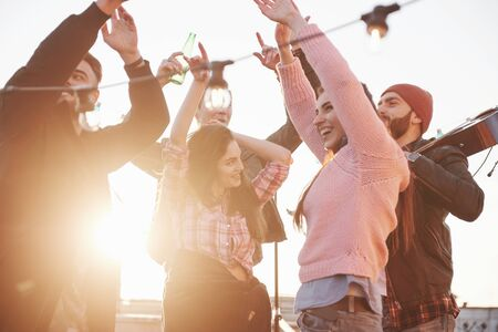 Conception of party. Hands up. Young people spend sunny autumn day on the roof with guitar and drinks.