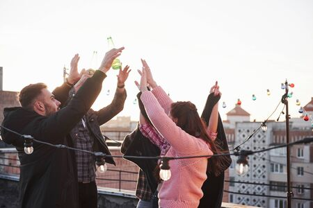 Its happiness. Hands up. Young people spend sunny autumn day on the roof with guitar and drinks.
