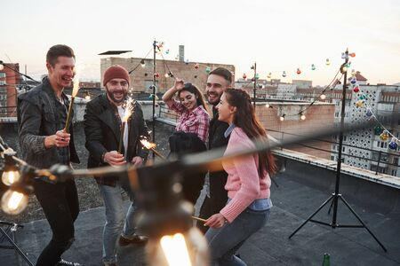 Happy holidays. Playing with sparklers on the rooftop. Group of young beautiful friends.