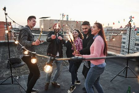 Enjoy the moment. Playing with sparklers on the rooftop. Group of young beautiful friends.