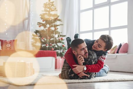 Beautiful lighting and great atmosphere. Lovely young couple lying on the living room with green holiday tree at background. Foto de archivo - 134747439