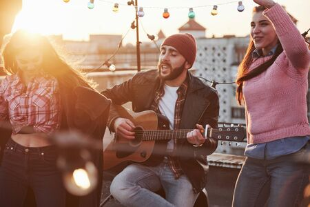 Feel the rhythm. Guitarist sits and singing for his friends at the rooftop with decorative colored light bulbs.