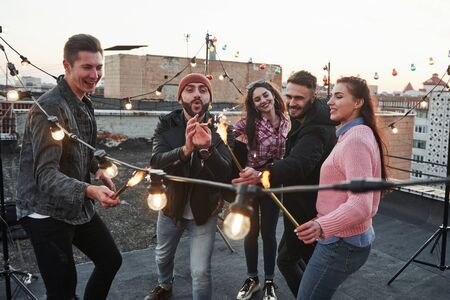 Playing with sparklers on the rooftop. Group of young beautiful friends.