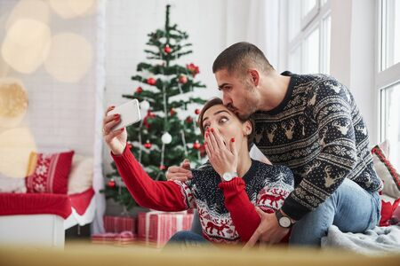 Emotional girl want funny photo. Happy young people sits on the windowsill in the room with christmas decorations. Foto de archivo - 134747575