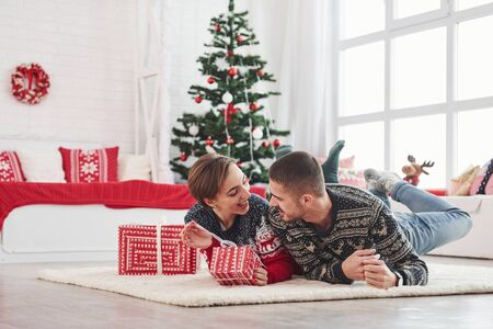 Lovely young couple lying on the living room with green holiday tree at background. Foto de archivo - 134747581