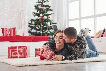 Guy gives his wife christmas gift. Lovely young couple lying on the living room with green holiday tree at background. Foto de archivo - 134747582