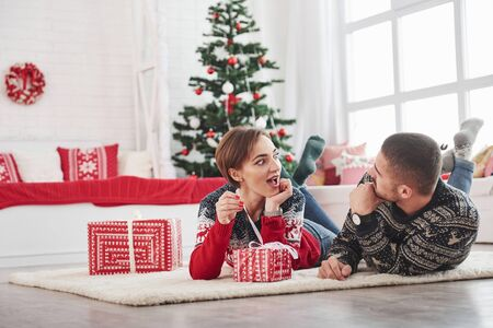 Girl is excited what kind of gift inside the box. Lovely young couple lying on the living room with green holiday tree at background. Foto de archivo - 134747584