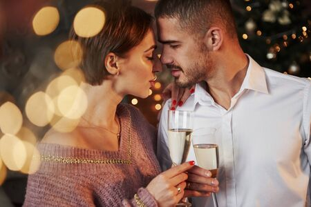 Desire is in the air. Nice couple celebrating new year indoors with classic beautiful clothes on they.