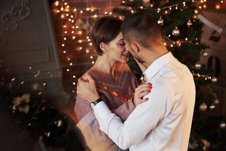 Reflection of the christmas tree. Closeness of the guy and girl in luxury wear that dancing and flirting.