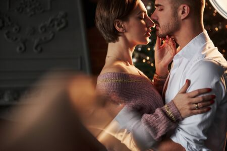 Woman looks at the lips. Closeness of the guy and girl in luxury wear that dancing and flirting. Imagens