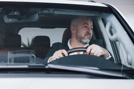 Looking to the side. Front view of senior businessman in his new modern car testing new functions.