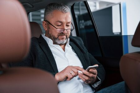 Contacting with colleagues. Using mobile phone. Businessman in the eyeglasses sits in the back of the modern car and have some deals.