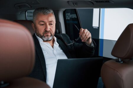 Preparing to read some documents. Working on a back of car using silver colored laptop. Senior businessman.