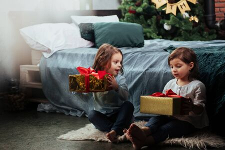 Gorgeous decorated bedroom. Christmas holidays with gifts for these two kids that sitting indoors in the nice room near the bed. 스톡 콘텐츠