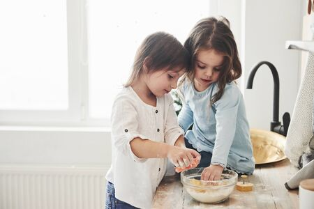 Preschool friends learning how to cook with flour in the white kitchen. Stok Fotoğraf