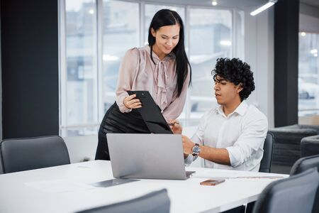 Guy explain meaning of document. Curly guy and brunette girl discusses the details of the contract in modern office.