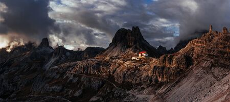 Nice landscape. Touristic buildings waiting for the people who wants goes through these majestic dolomite mountains. Panoramic photo.